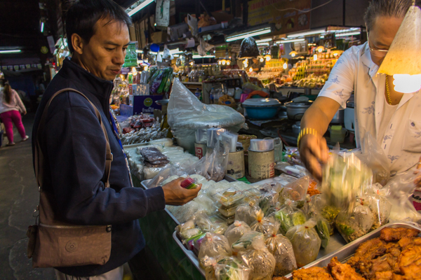 James in the market choosing which foods to give the monks.