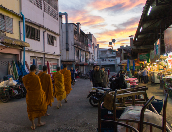 Monks walking through the public market at sunrise.